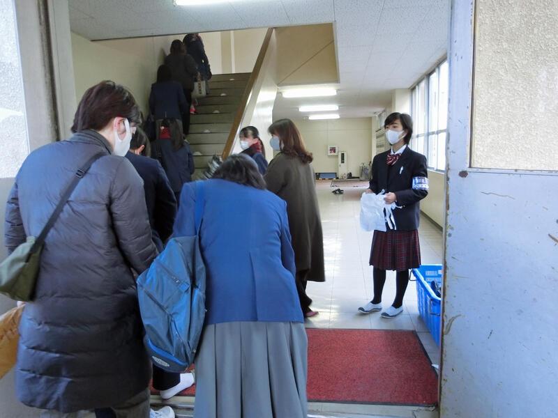 入口で来場者を迎える生徒会長